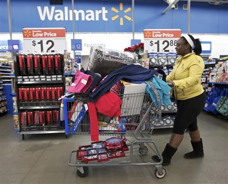 A woman with a full shopping cart heads to the checkout at a Wal-Mart Store in Chicago in this file photo taken November 23, 2012. Wal-Mart Stores Inc posted a higher quarterly profit and raised its dividend payout on Thursday, as efforts such as extending its layaway program and matching competitors' prices attracted shoppers during the competitive holiday season. REUTERS/John Gress/Files