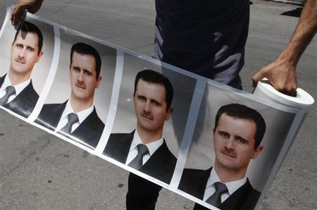 A man holds a roll of pictures of Syrian President Bashar al-Assad during a rally in support of him at al-Umawiin square in Damascus June 21, 2011. REUTERS/Khaled al-Hariri
