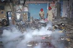 Unos bomberos apagan las llamas de un incendio en el sitio de una explosión en Hyderabad, India, feb 21 2013. Al menos 11 personas murieron y 50 resultaron heridas el jueves tras la explosión de dos bombas instaladas en bicicletas en un concurrido mercado en la sureña ciudad india de Hyderabad, informó el Gobierno. REUTERS/Stringer