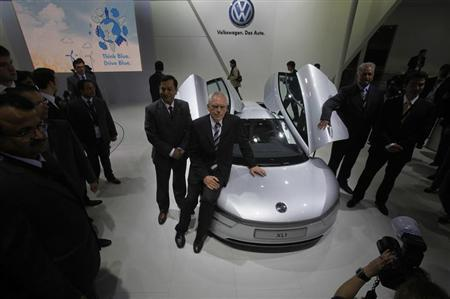 Volkswagen member of the Board of VW brand Technical Development Dr. Ulrich Hackenberg poses with company's XL1 hybrid concept car during India's Auto Expo in New Delhi January 5, 2012. REUTERS/Adnan Abidi