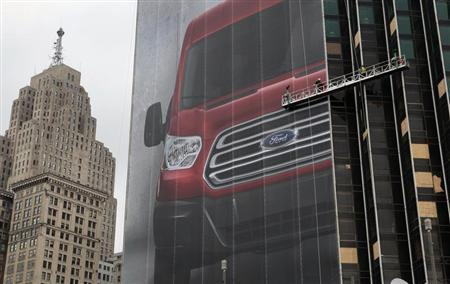 Workers hang a Ford Motor banner on the side of a building across from Cobo Center in advance of the media preview of the North American International Auto show in Detroit, Michigan January 11, 2013. REUTERS/Rebecca Cook