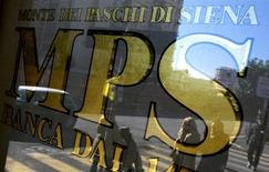 Passanti riflessi nella vetrata di una filiale romana del Monte dei Paschi. REUTERS/Max Rossi
