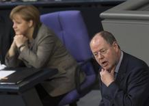 Peer Steinbrueck (R), the candidate for chancellor of the Social Democratic Party (SPD), in this year's general election, responds to German Chancellor Angela Merkel's government policy statement about her EU policy during a session of the Bundestag, the lower house of parliament in Berlin February 21, 2013. REUTERS/Thomas Peter (GERMANY - Tags: POLITICS)