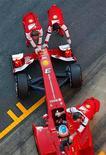 El piloto español de Ferrari Fernando Alonso mantuvo contentos a los aficionados en casa marcando el jueves el tiempo más rápido en las pruebas de pretemporada en el Circuito de Cataluña. En la imagen, mecánicos empujan el coche del piloto español de Fórmula 1 Fernando Alonso, de Ferrari, en una sesión de entrenamiento en el Circuito de Cataluña en Montmeló, cerca de Barcelona, el 20 de febrero de 2013. REUTERS/Albert Gea