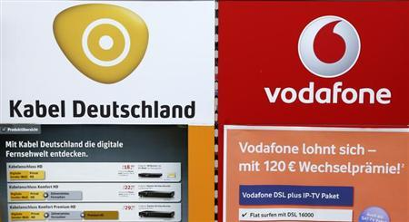 An advertising billboard of Germany's biggest cable operator Kabel Deutschland and mobile operator Vodafone is pictured in a shop in Berlin February 20, 2013. Kabel Deutschland is to hike its dividend 67 percent in a move which some traders and investors saw as a first defensive jab to ward off a possible 10 billion euros ($13.4 billion) bid from Vodafone. REUTERS/Fabrizio Bensch (GERMANY - Tags: BUSINESS TELECOMS)