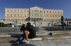 A couple kiss in front of the parliament building during an anti-austerity rally in central Athens November 14, 2012. REUTERS/John Kolesidis