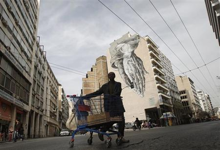 An immigrant living in Greece pushes a shopping trolley with scrap in front of a building covered with street art in Athens February 4, 2013. REUTERS/John Kolesidis