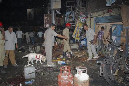 Investigating officers use a sniffer dog as they inspect the site of an explosion at Dilsukh Nagar, in Hyderabad February 21, 2013. REUTERS/Stringer