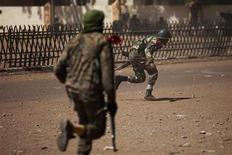 Soldats maliens cherchant à se mettre à couvert lors de combats avec des islamistes présumés à Gao. La situation est revenue à la normale à Gao, la plus grande ville du nord du Mali, après des combats qui ont opposé jeudi les forces françaises et maliennes aux djihadistes, a affirmé le ministre français de la Défense Jean-Yves Le Drian, en déplacement à Bruxelles. /Photo prise le 21 février 2013/REUTERS/Joe Penney