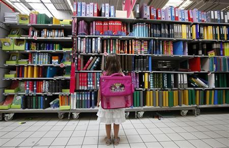 A young girl looks at school stationery in a supermarket in Nice August 23, 2012. REUTERS/Eric Gaillard