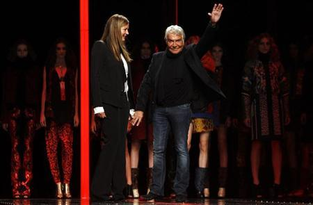 Italian designer Roberto Cavalli (R) and his wife Eva acknowledge the applause on the catwalk at the end of the Just Cavalli Autumn/Winter 2013 collection at Milan Fashion Week February 21, 2013. REUTERS/Alessandro Garofalo