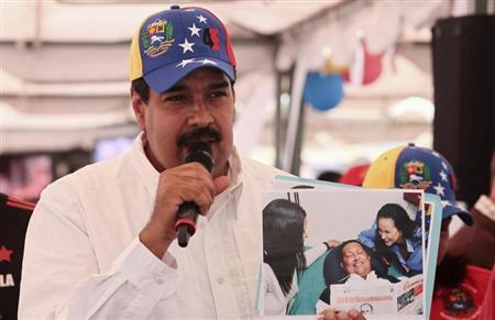 Venezuelan Vice President Nicolas Maduro holds up a copy of a picture of President Hugo Chavez while speaking to supporters at a market in Caracas February 16, 2013. REUTERS/Miraflores Palace/Handout