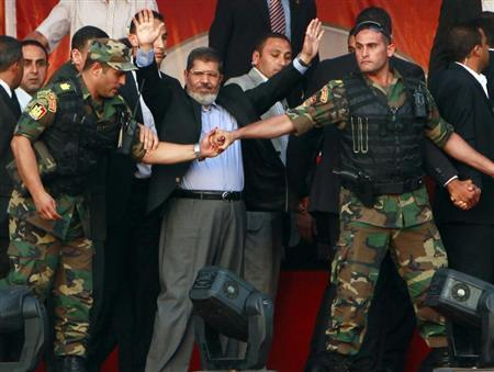 Egypt's Islamist President-elect Mohamed Mursi waves to his supporters while surrounded by his members of the presidential guard in Cairo's Tahrir Square, June 29, 2012. REUTERS/Amr Abdallah Dalsh