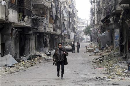 A member of the Free Syrian Army carries weapons while walking down a debris-filled street in Aleppo's district of Salaheddine February 19, 2013. REUTERS/Abdalghne Karoof