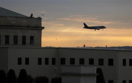 A commercial plane flies past the Pentagon as security watch from the roof September 11, 2008. REUTERS/Jason Reed