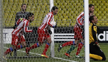 Atletico Madrid's Falcao (L) celebrates his goal with team mates, while Rubin Kazan's goalkeeper Sergei Ryzhikov (R) kneels down nearby, during their Europa League soccer match at the Luzhniki stadium in Moscow, February 21, 2013. REUTERS/Maxim Shemetov