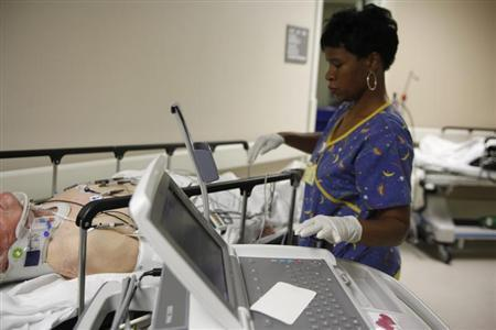 EKG technician Diana Goodie (R) performs an electrocardiogram on a patient in the hallway of the emergency room at Ben Taub General Hospital in Houston, Texas, July 27, 2009. REUTERS/Jessica Rinaldi