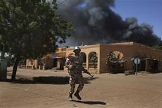 A Malian soldier runs past smoke from a petrol station on fire during fighting with Islamists in Gao February 21, 2013. REUTERS/Joe Penney