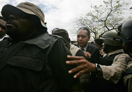 Former dictator Jean-Claude ''Baby Doc'' Duvalier is escorted into the Palace of Justice in Port-au-Prince January 18, 2011.
