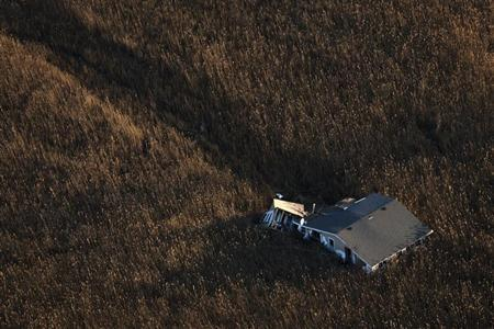 An aerial view shows a house pushed into marshland almost a month after the Oakwood neighborhood in the Staten Island borough of New York was left devastated by Hurricane Sandy, November 28, 2012. REUTERS/Adrees Latif
