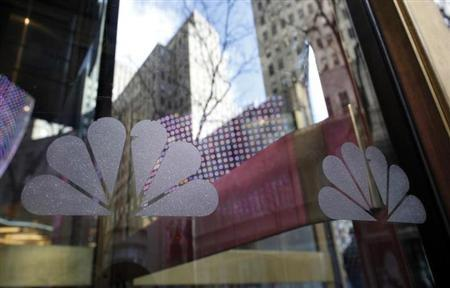 NBC logos are seen on a door with buildings around Rockefeller Center reflected in the background at the home of NBC's studios, in New York, December 3, 2009. REUTERS/Chip East/Files