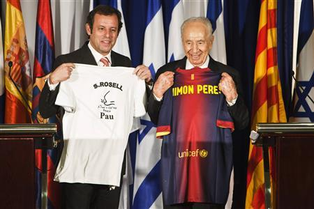 Israel's President Shimon Peres (R) and President of Barcelona soccer team Sandro Rosell hold t-shirts which they gave one other as gifts during a news conference in Tel Aviv February 21, 2013. REUTERS/Nir Elias