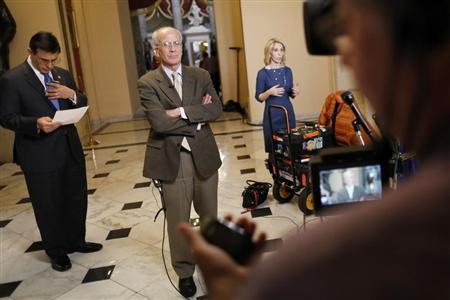 U.S. Representative Darrell Issa (R-CA) (left) reads notes about a possible deal in the Senate as he and Representative Peter Welch (D-VT) (center) stand for separate television interviews at the U.S. Capitol in Washington December 31, 2012. REUTERS/Jonathan Ernst
