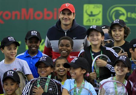 Roger Federer of Switzerland poses with the Qatari Tennis team children during the opening of the Qatar Open tennis tournament in Doha in this January 3, 2011 file photo. REUTERS/Jamal Saidi/Files