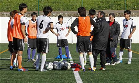 China's soccer players listen to coaches during their practice at a training session in Royal Queluz Massama pitch on the outskirts of Lisbon February 15, 2013. REUTERS/Jose Manuel Ribeiro