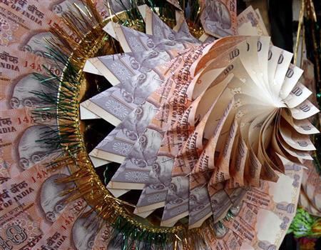 Rupee notes are stapled to form a garland at a market in Srinagar May 20, 2008. REUTERS/Fayaz Kabli/Files