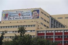 El presidente venezolano, Hugo Chávez, aún sufre problemas respiratorios tras la cuarta cirugía por cáncer que se realizó en Cuba en diciembre, dijo el jueves el Gobierno. En la imagen, un cartel con la fotografía del presidente Hugo Chávez aparece en la fachada del hospital militar tras el inesperado regreso del mandatario venezolano, en Caracas, el 18 de febrero de 2013. REUTERS/Jorge Silva