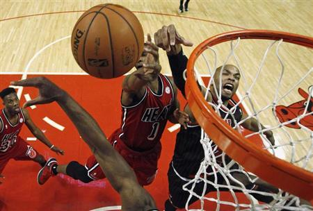 Chicago Bulls' Taj Gibson (R) is guarded by Miami Heat's Chris Bosh (C) during the second half of their NBA basketball game in Chicago, Illinois, February 21, 2013. REUTERS/Jim Young