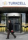 Человек проходит мимо входа в головной офис Turkcell в Стамбуле 14 мая 2009 года. Чистая прибыль крупнейшего турецкого телекоммуникационного оператора Turkcell выросла на 38 процентов до 459 миллионов лир ($257 миллионов) в четвертом квартале 2012 года, превысив прогнозы. REUTERS/Osman Orsal