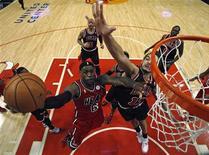 LeBron James (à gauche) du Miami Heat monte au panier malgré l'opposition de Joakim Noah des Chicago Bulls. Le tenant du titre a signé jeudi soir sur le parquet des Chicago Bulls une neuvième victoire d'affilée (86-67) qui conforte son emprise sur la conférence Est de la NBA, le championnat nord-américain de basket. /Photo prise le 21 février 2013/REUTERS/Jim Young