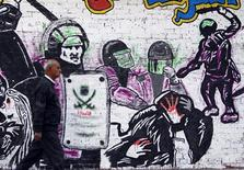 El presidente Mohamed Mursi programó el jueves las elecciones parlamentarias en Egipto entre el 27 de abril y finales de junio, en unos comicios de cuatro etapas con los que el líder islamista espera poner fin a la turbulenta transición democrática en el país del norte de África. En la imagen, un hombre pasa por delante de un graffiti que denuncia la violencia policial en la calle Mohamed Mahmud Street, cerca de la Plaza Tahrir, en El Cairo, el 19 de febrero de 2013. REUTERS/Amr Abdallah Dalsh