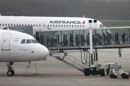 Passengers walk through an aerobridge to embark an Air France plane on the tarmac of Charles de Gaulles International Airport in Roissy near Paris, January 8, 2013. Investors in Alitalia who helped rescue the airline four years ago are considering selling their shares, with some pushing for a deal with long-time stakeholder Air France-KLM, sources with knowledge of the situation said on Monday, January 7, 2013. REUTERS/Charles Platiau (FRANCE - Tags: TRANSPORT BUSINESS) - RTR3C7OL