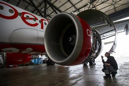 An Air Berlin technician inspects the jet engine of an Air Berlin plane at a hangar at Tegel Airport in Berlin, January 16, 2013. German airline Air Berlin , part-owned by Abu Dhabi-based carrier Etihad, plans to cut almost 10 percent of its workforce of 9,300 as part of a cost-cutting campaign aimed at halting years of losses. REUTERS/Thomas Peter (GERMANY - Tags: TRANSPORT BUSINESS) - RTR3CIV1