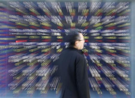 A man looks at a stock index board outside a brokerage in Tokyo January 18, 2013. REUTERS/Kim Kyung-Hoon/Files