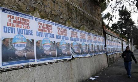 A man walks past election campaign posters of PDL (People of Freedom) member Silvio Berlusconi in Rome, February 21, 2013. REUTERS/Stefano Rellandini