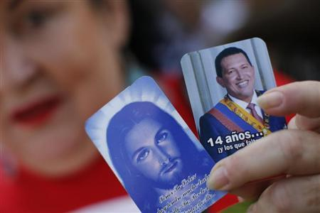A supporter of Venezuela's President Hugo Chavez holds pictures of Jesus Christ and Chavez outside the military hospital after his surprise return to Caracas February 18, 2013. REUTERS/Jorge Silva
