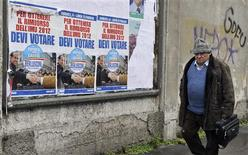 A man walks past election campaign posters of PDL (People of Freedom) member Silvio Berlusconi in Milan, February 21, 2013. REUTERS/Paolo Bona