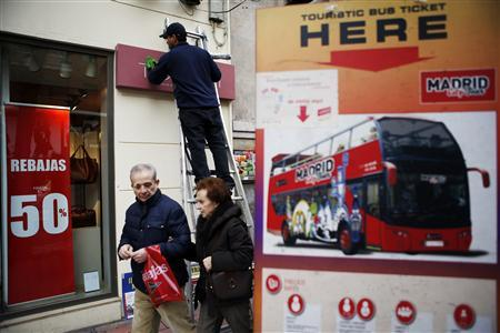 A worker cleans the exteriors of a shop near sales advertisements as people walk by in Madrid January 11, 2013. REUTERS/Susana Vera