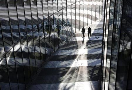 Two men walk past the headquarters of the German postal and logistics group Deutsche Post AG in Bonn March 9, 2010. REUTERS/Ina Fassbender (GERMANY - Tags: BUSINESS IMAGES OF THE DAY