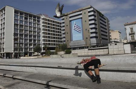 A woman lies at central Omonia Square in Athens October 17, 2012. A Greek exit from the euro zone could trigger a global economic crisis of dire proportions and must be avoided at all costs, a respected German think tank said in a study published on Wednesday. REUTERS/John Kolesidis (GREECE - Tags: POLITICS BUSINESS) - RTR398WB