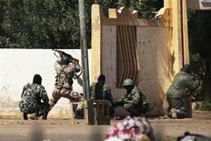 Militaires maliens à l'assaut de la mairie de Gao, jeudi. Une quinzaine d'islamistes ont été tués, deux soldats français très légèrement blessés et quatre soldats maliens blessés lors des combats de jeudi pour déloger de la mairie de la plus grande ville du nord du Mali des combattants islamistes infiltrés pendant la nuit. /Photo prise le 21 février 2013/REUTERS/Joe Penney