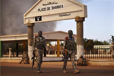 Malian soldiers walk past French soldiers crouching near Sharia Square, now renamed Independence Plaza, during fighting with Islamists in Gao, February 21, 2013. REUTERS/Joe Penney