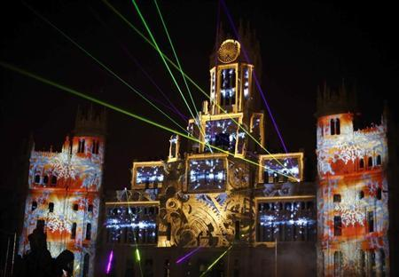 Laser beams and images are projected on the facade of Madrid's city hall during a lighting show to mark the start of Christmas festivities in the Spanish capital of Madrid December 23, 2012. REUTERS/Sergio Perez