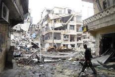 Noventa personas murieron el jueves por cuatro bombardeos ocurridos en Damasco, dijo un grupo que monitorea la violencia en el país, con lo cual se convirtió en uno de los días más sangrientos en la capital de Siria desde que la revuelta contra el presidente Bashar el Asad estalló hace dos años. En la imagen, un miembro del Ejército Libre Sirio porta un arma mientras anda por una calle destruida por los combates en el distrito de Salaheddine de Alepo, el 19 de febrero de 2013. REUTERS/Abdalghne Karoof