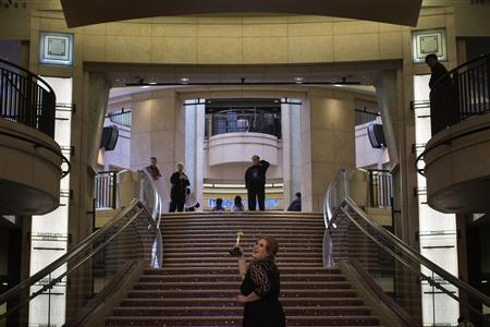 A woman poses for photos along the steps leading to the Dolby Theatre, the site for the 85th Academy Awards in Los Angeles, California February 21, 2013. REUTERS/Adrees Latif