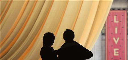 A couple is silhouetted against a golden drape overlooking red carpet preparations ahead of the 85th Academy Awards in Los Angeles, California February 21, 2013. REUTERS/Adrees Latif